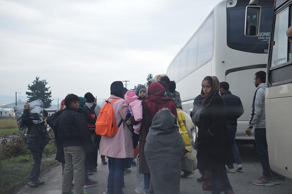 Ώρα 07.15, πρωί Πέμπτης, 9 βαθμοί Κελσίου. Μόλις έφτασε ένα ακόμη πούλμαν από τα εκατοντάδες που ξεκινούν καθημερινά από Αθήνα και Θεσσαλονίκη. Οι πρόσφυγες σφίγγουν τα μπουφάν (όσοι έχουν, πολλοί κυκλοφορούν ακόμη και με σαγιονάρες), καπνίζουν ένα τσιγάρο, πολλοί κατουράνε στα χωράφια στην άκρη του στενού δρόμου. Παρά την κούραση, την πείνα και την αγωνία για το θα συμβεί εκεί, μας χαιρετούν καθώς περνάμε με το αμάξι δίπλα τους.